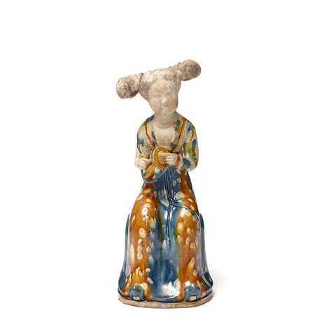 A earthenware court lady is sitting on an seat with a couple of small gongs in her hands. She slightly crooks her head and smiles.