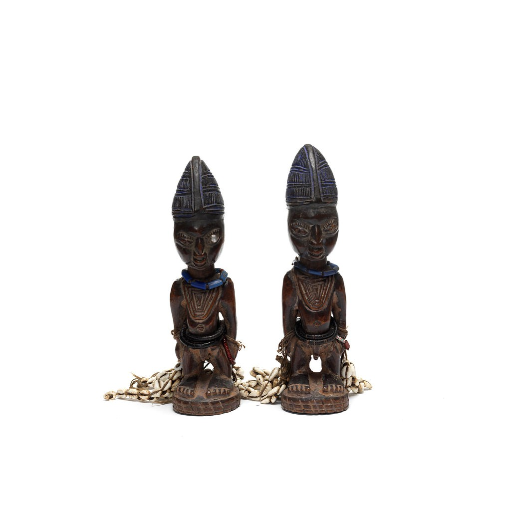 Two wooden male twin figure. Their hands are holding two shell strings.