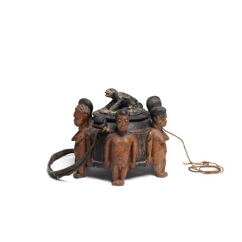 A wooden bowl which is surrounded by six people. Here's an animal on the top of it.