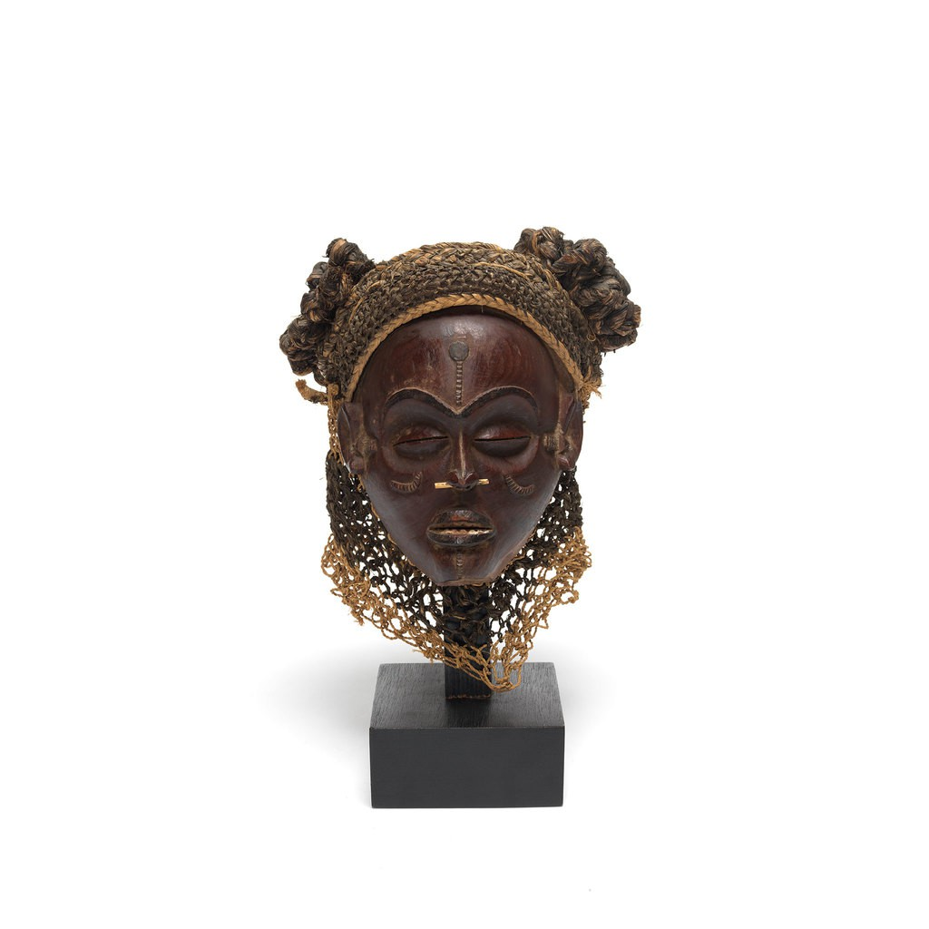 A wooden female head portrait.