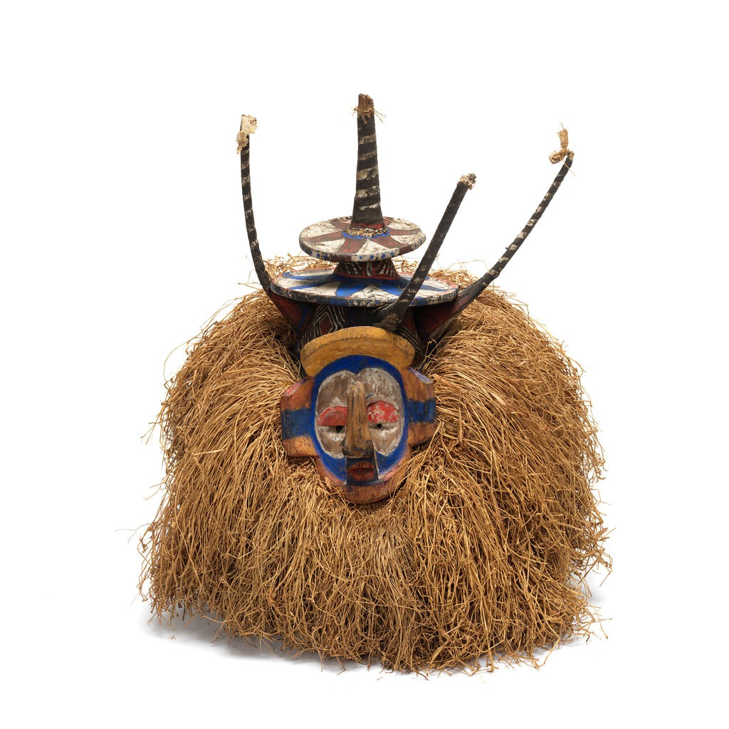 A mask which has a colorful face and a big amount yellow hair.