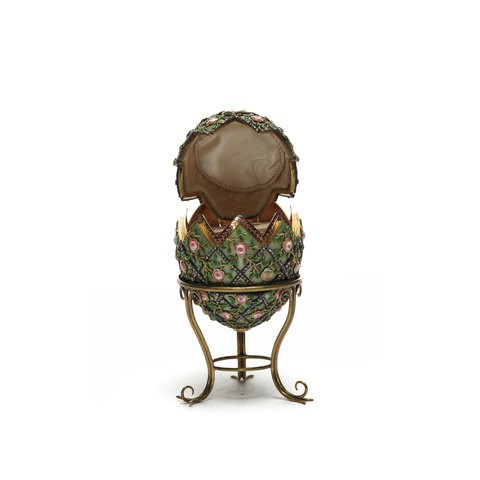 An green enamel egg with gold rose trellis and diamond decoration on it.
