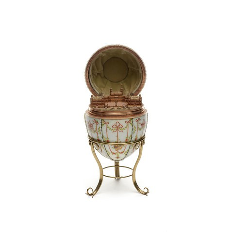 A white enamel egg which is decorated by diamonds. Inside of the egg, here's a delicate castle sculpture.