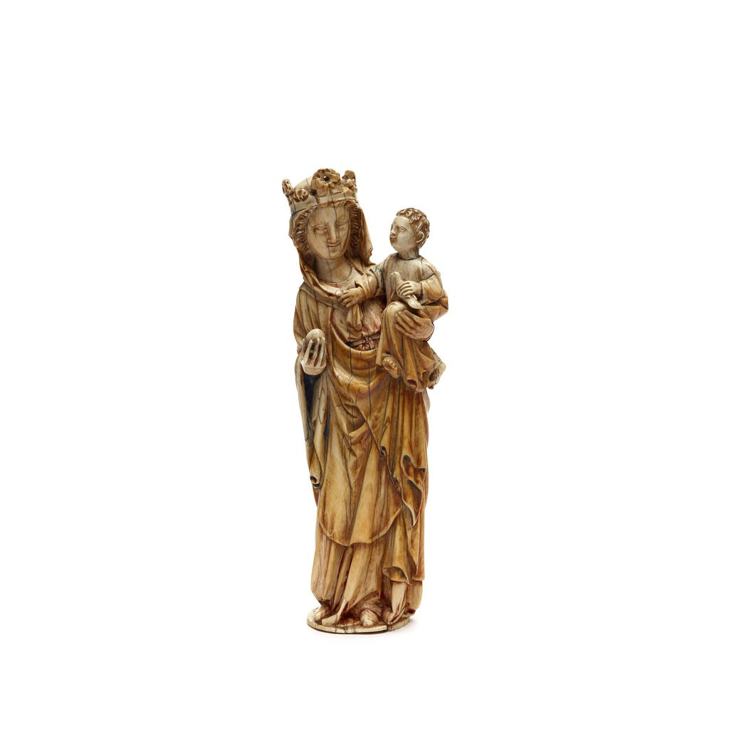 A Ivory Virgin and Child sculpture. The Virgin supports the Child with her left hand, and the Child grasps the end of her head cloth and holds a bird.
