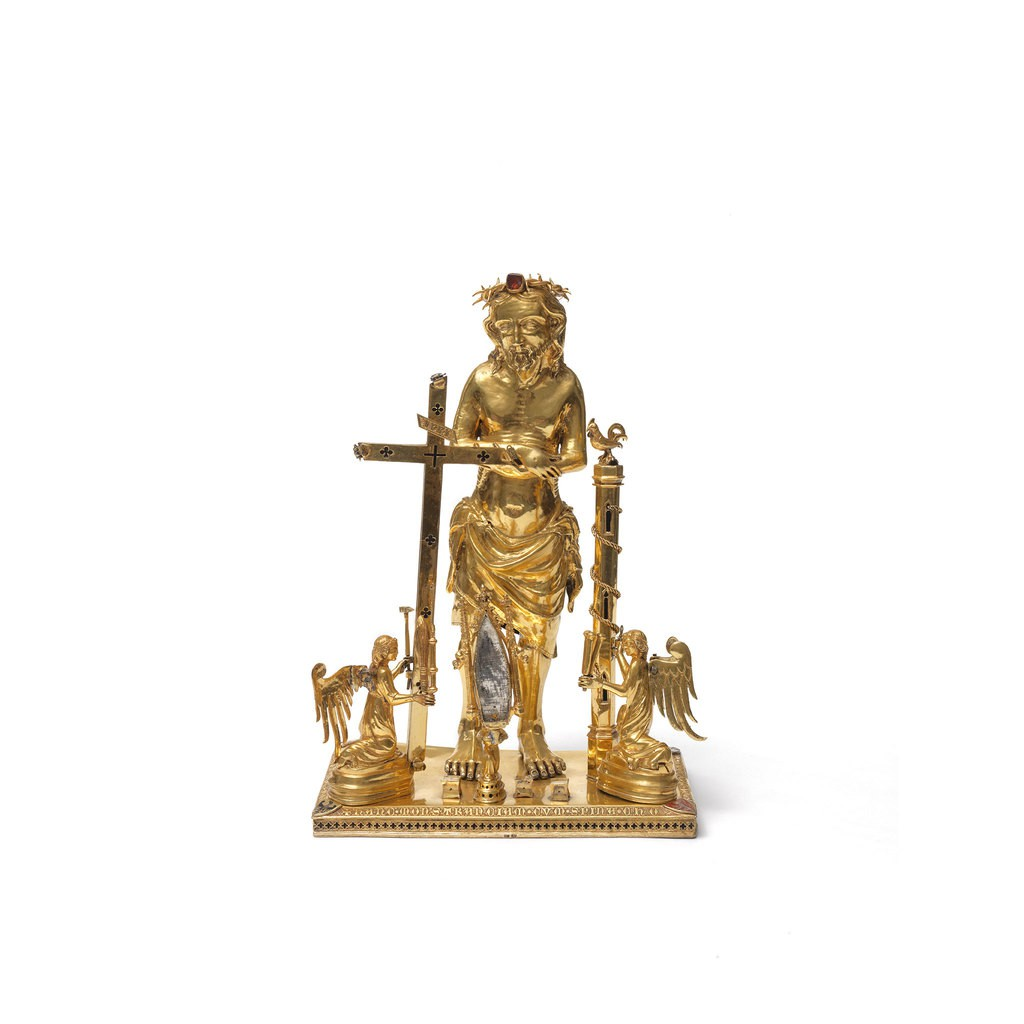 A gold portrait sculpture which presents a male standing in front of a cross. There are two angels are kneeing beside him.