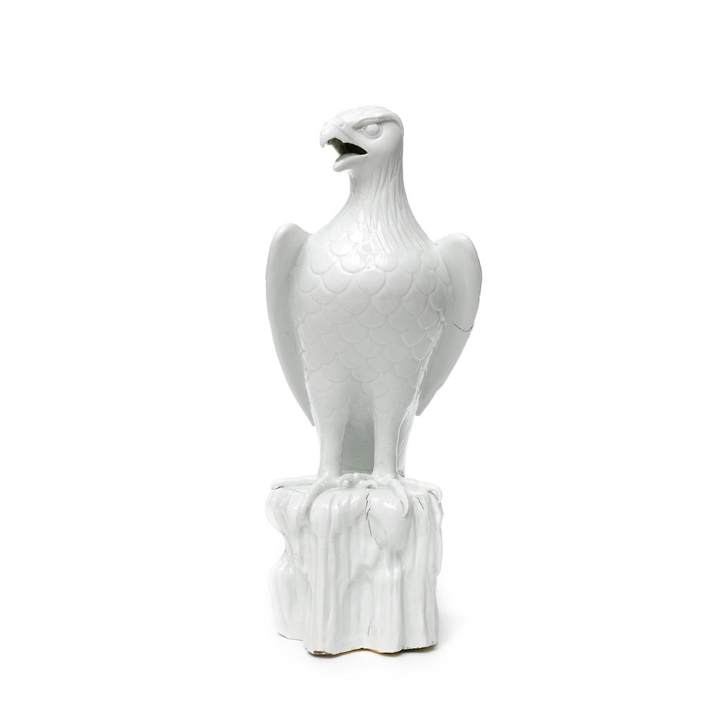 A white porcelain eagle. It has delineated plumage, his head slightly turned and beak open, with his wings furled and tail lowered. It is perched on a craggy rock with talons curled over the edge.
