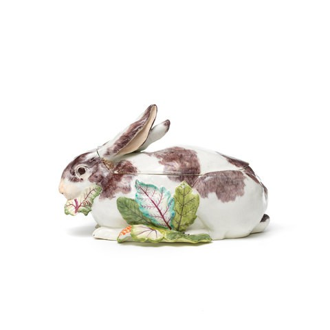 A white and brown porcelain rabbit is eating a leaf of lettuce. The lid encompasses the ears and part of the back of the rabbit.