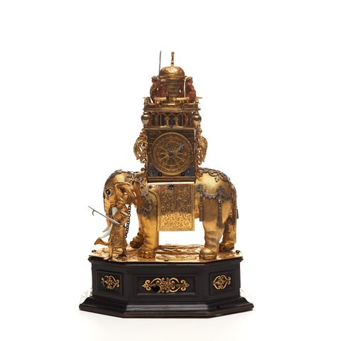 A golden elephant standing on a wooden stand. It is carrying a clock on his back.