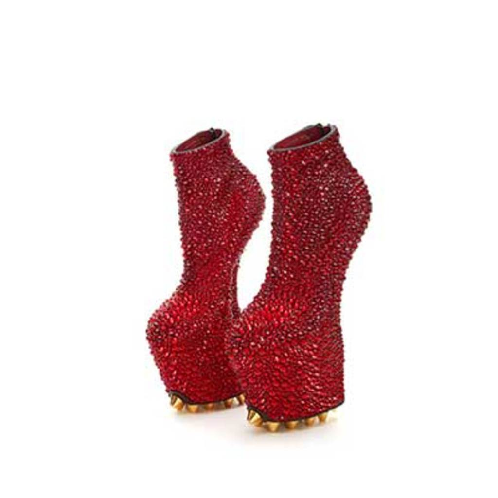 A pair of red high heel boots are covered by Rhinestones.