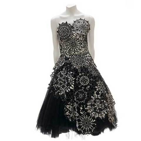 A black and white dress which has different sizes snowflakes on it.
