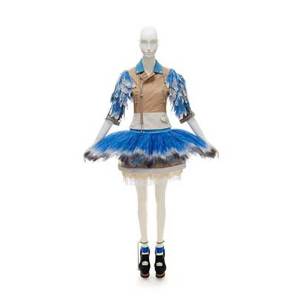 A blue dress which's top is a brown leather jacket. The sleeves are covered by blue feathers. The skirt is a blue  ballet skirt.