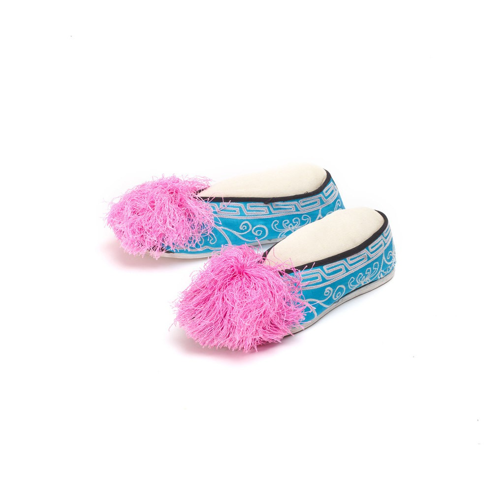 A pair of blue fabric shoes. Each shoe has one pink pompon in the front.