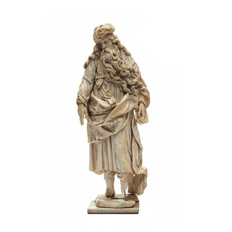 A long-hair and beard male figure sculpture which presents a prophet in a robe. His two fingers are pointing to the ground..