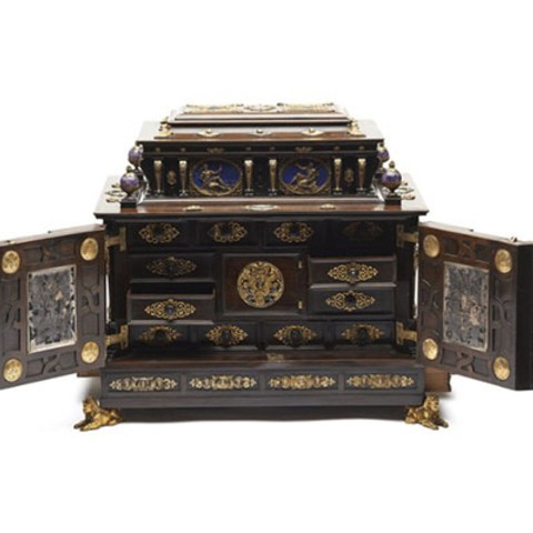 A delicate wooden chest Inside of the chest, there are several small drawers.