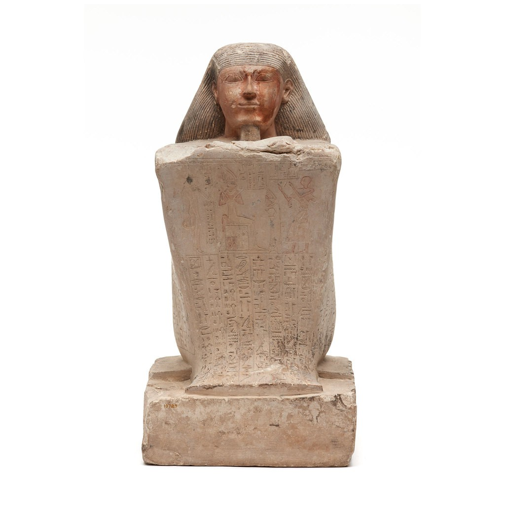This stately sculpture represents a priest of Hathor named Basa, seated with his cloak drawn over his knees. The surface is covered with a record of the names and titles of 26 generations of Basa's paternal family.
