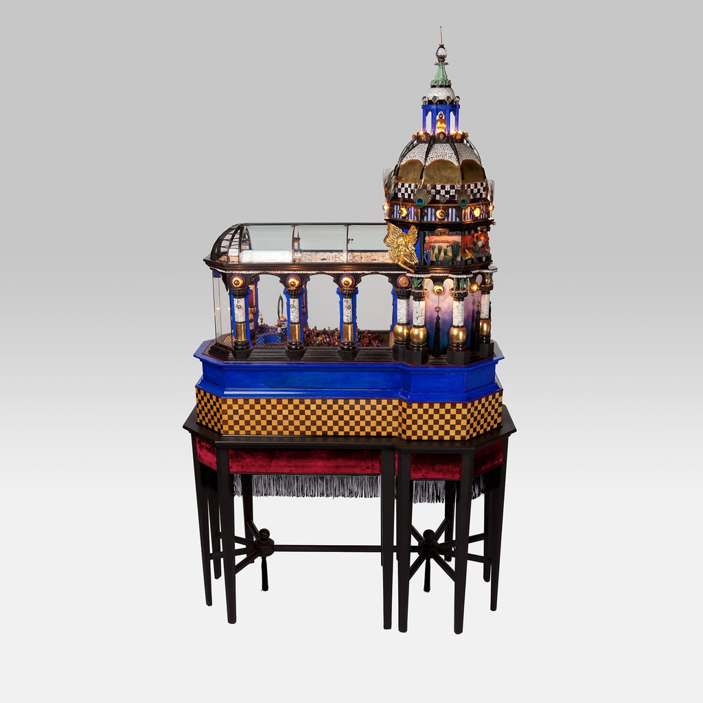 An elaborate kinetic sculpture which presents a movie palace. All the details such as the posters, popcorn machine, lamps, different types of audience are presented very well.