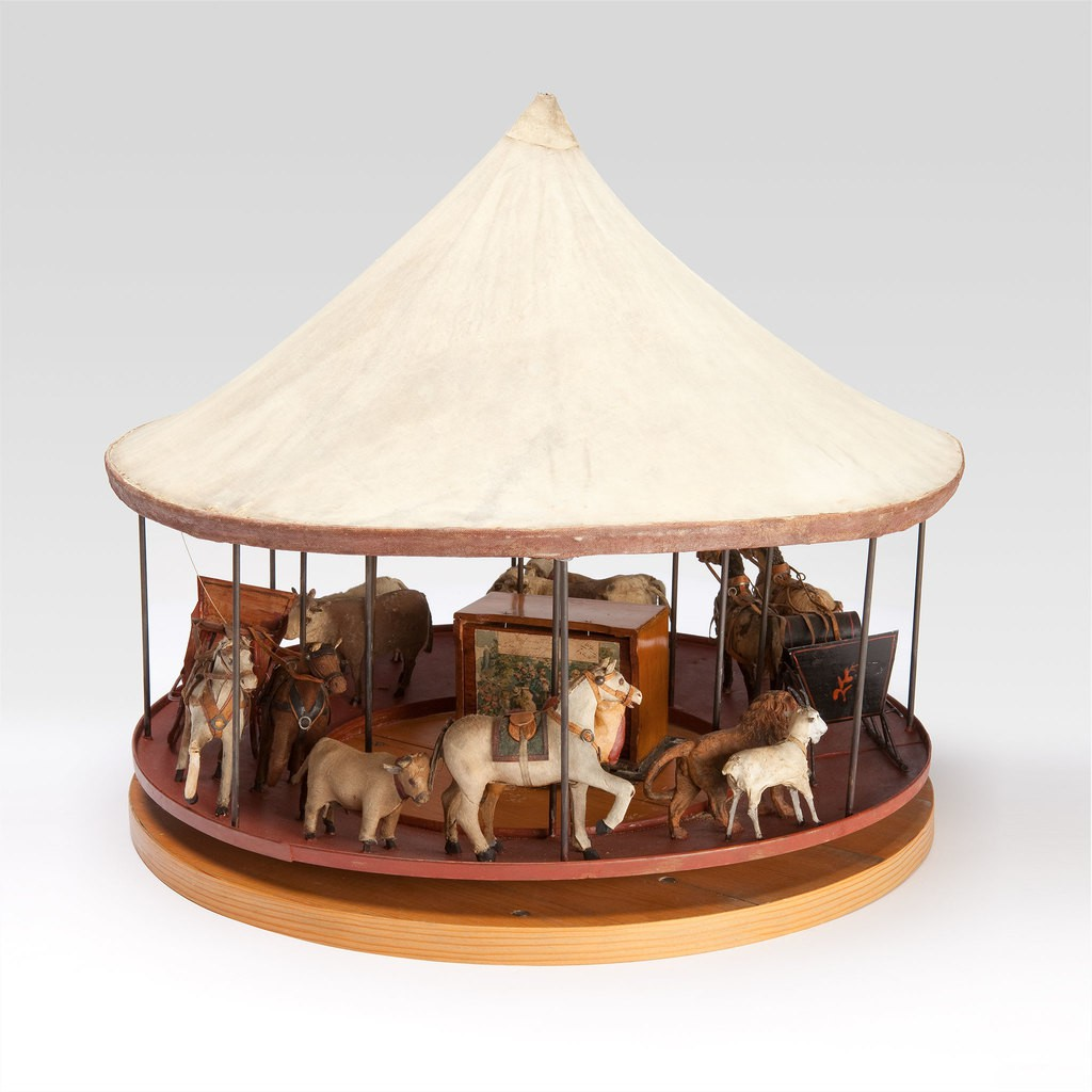 A sculpture of a merry-go-round. In side of it, there are multiple animals such as goats, cows, horses, lions and camel.