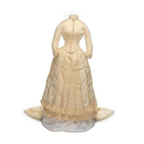 An ivory colour dress which is closed with eighteen buttons. The generous skirt is decorated with a panel silk plush, finished with a pleated frill.