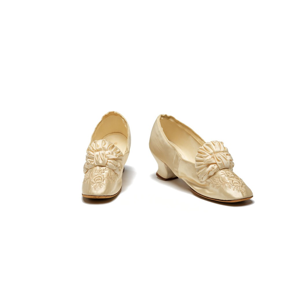 A ivory-color fabric covered high heal shoes.