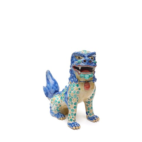 A porcelain lion dog which is covered by blue, green and yellow pattern. It is opening its mouth like roaring.
