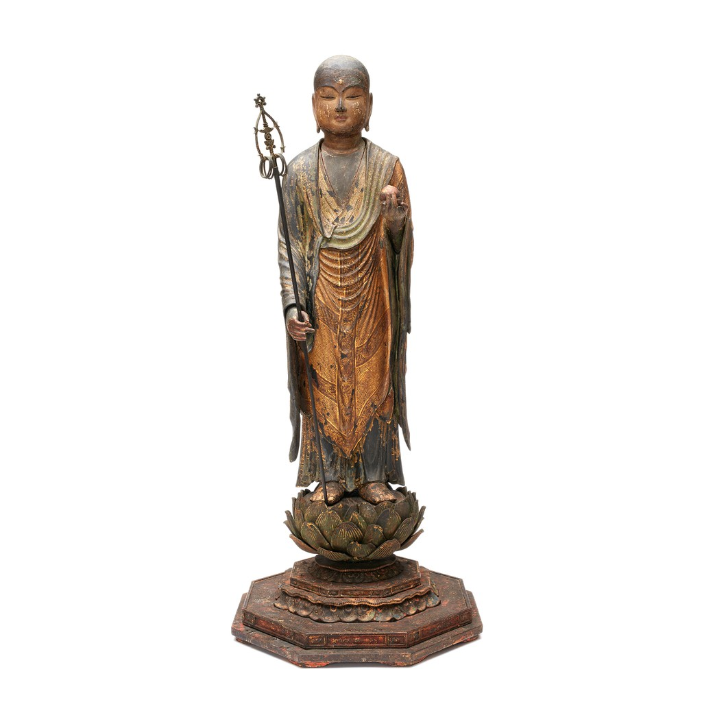 A wooden Bodhisattva sculpture is standing on a lotus-shape stand. His right hand is holding a six-ring staff, the other hand is holding wish-granting jewel.
