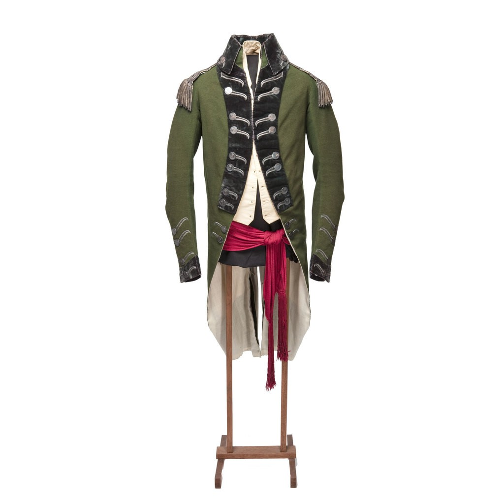 A green military uniform which has buttons in front. A red fabric bend crosses the waist part.