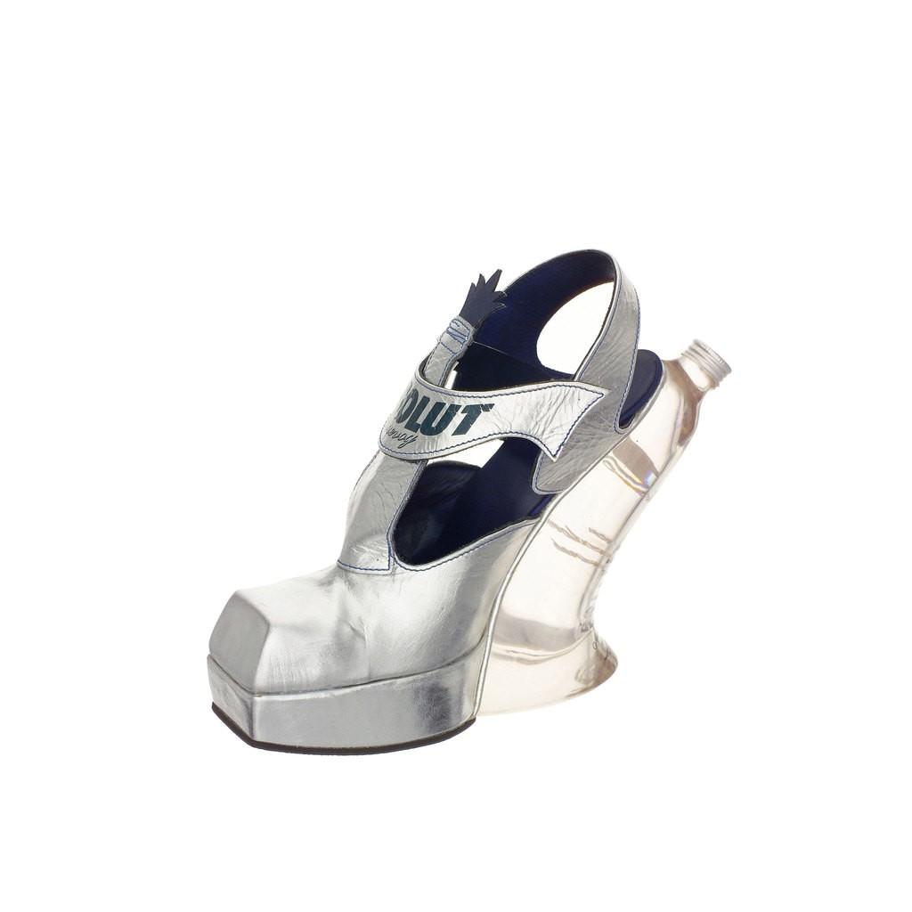 A silver high heel shoe. The heel part is a distorting vodka bottle.