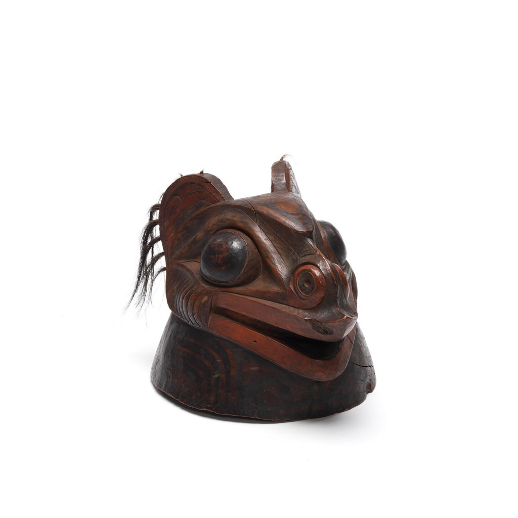 A Tlingit War Helmet. The design shows an animal head which has big eyes and ears with hair.