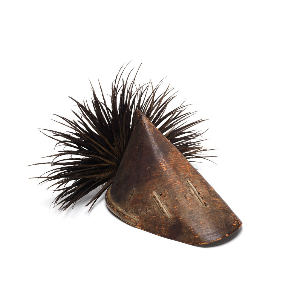 A brown triangular body hat which has careful arrangement black feathers at the end of the hat.