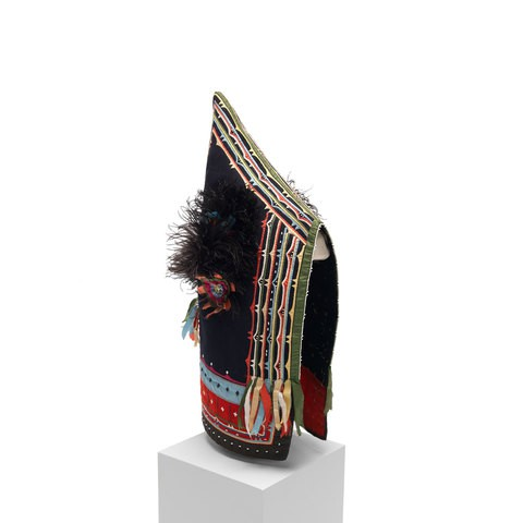 A black peaked cap with colorful fabric and black feathers decoration on it.
