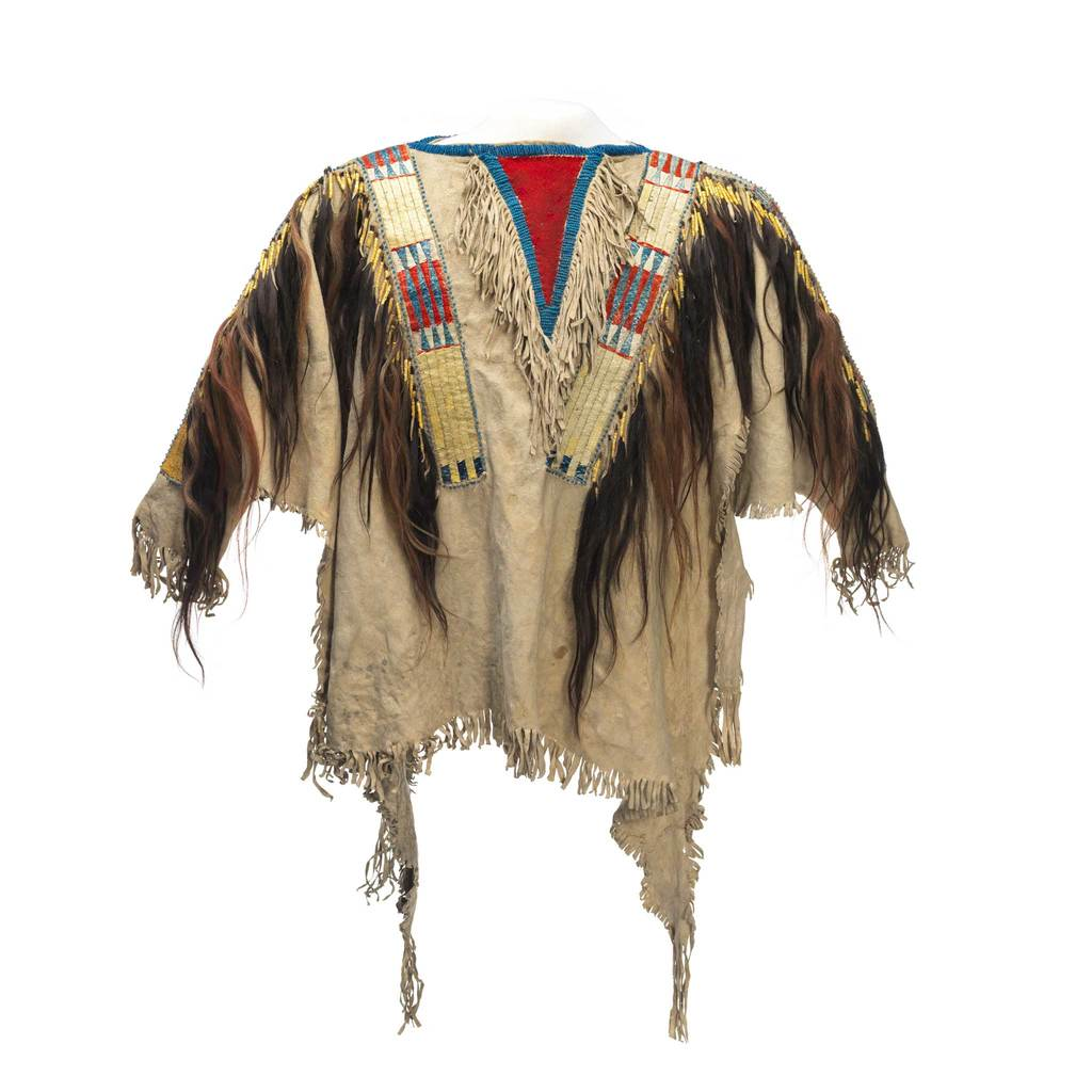 A yellow men's shirt which is decorated by colourful beads, animal hair and fabric strips.