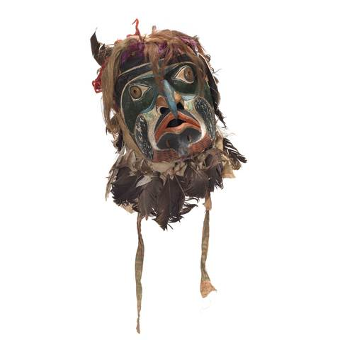 Bakwas mask, beak-like blue hooked nose, perforated brass disk for eyes surrounded by dark green patches, red, white and black facial markings, head covering of feathers mixed with hair, brightly colour ribbons and cloth, sharp pointed ears.
