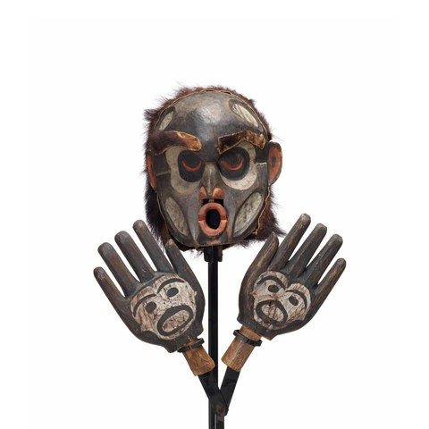 A Dzunukwa or wild woman of the woods mask with hands attached to mount, pursed lips painted red, mostly black with white paint details on face and hands.