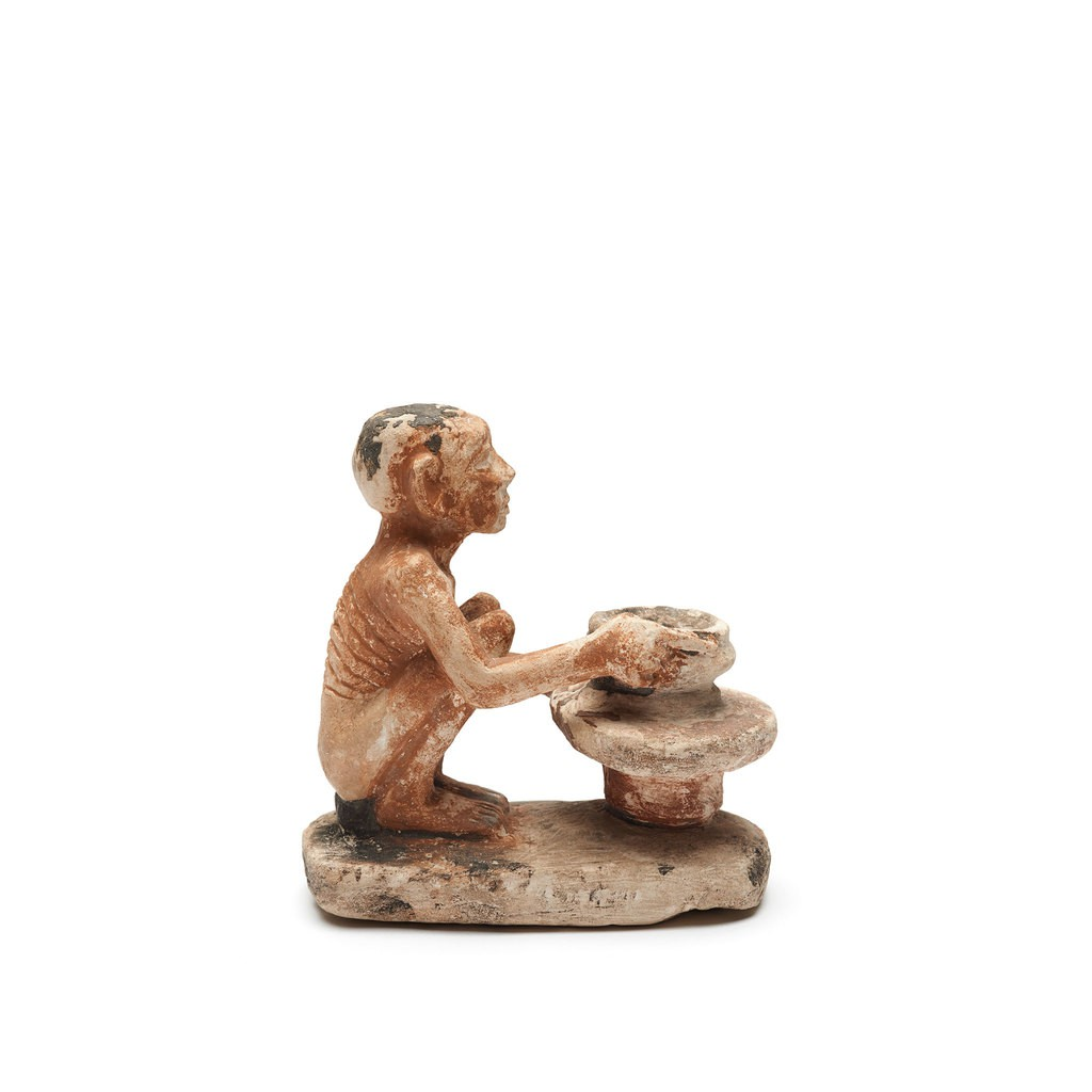 A sculpture is presenting a potter is working. The arduousness of his profession is indicated by the way his ribs stand out on his back, how his skin is tightly drawn over his face, and by his deeply receded hairline.