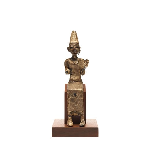 A bronze and covered with gold leaf Canaanite Statuette sculpture is seating. He is wearing a long head, his left hand is holding a fan-shaped piece.