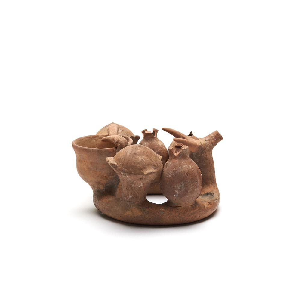 A baked clay Kernos Ring. It consists of a hollow clay ring with hollow clay attachments in the forms of a gazelle head, two jars, two pomegranates, two doves, and a cup. The doves, whose heads have been restored, drink from the cup. An eighth attachment is missing, having been broken off in antiquity.