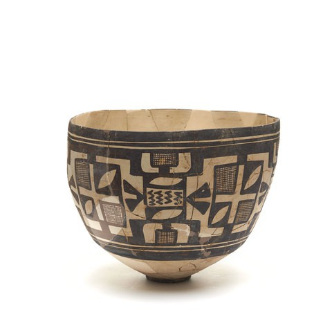 A baked clay bowl which is painted with black abstract patterns on the cover.
