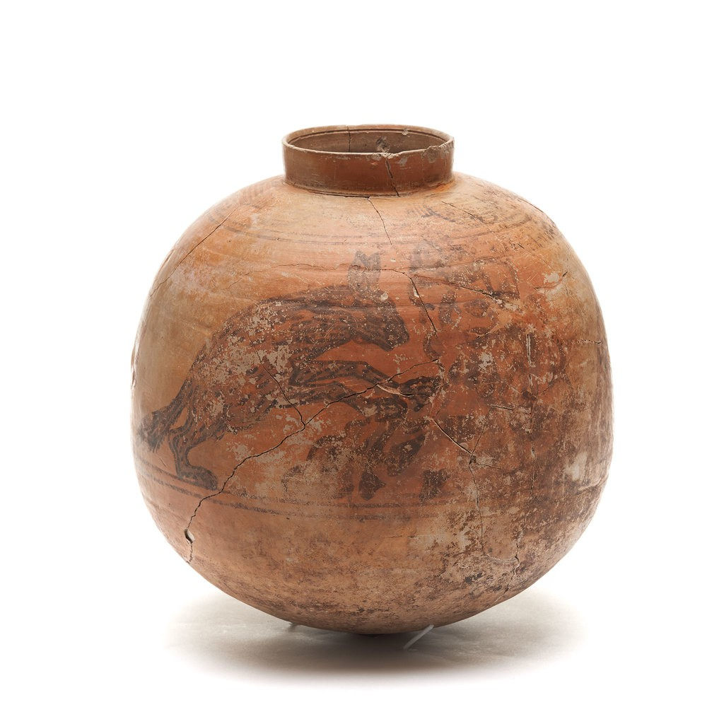 A clay Jar with animals patterns on it.
