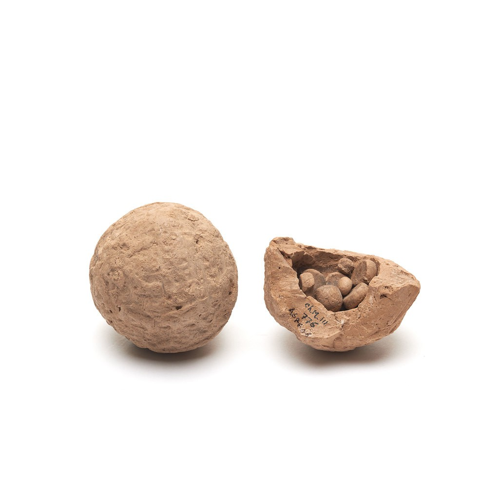 """Two clay ball marked with an official's seal. The ball encloses clay """"tokens"""""""