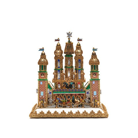 A delicate golden and silver castle sculpture. People are surrounding it and dancing together.