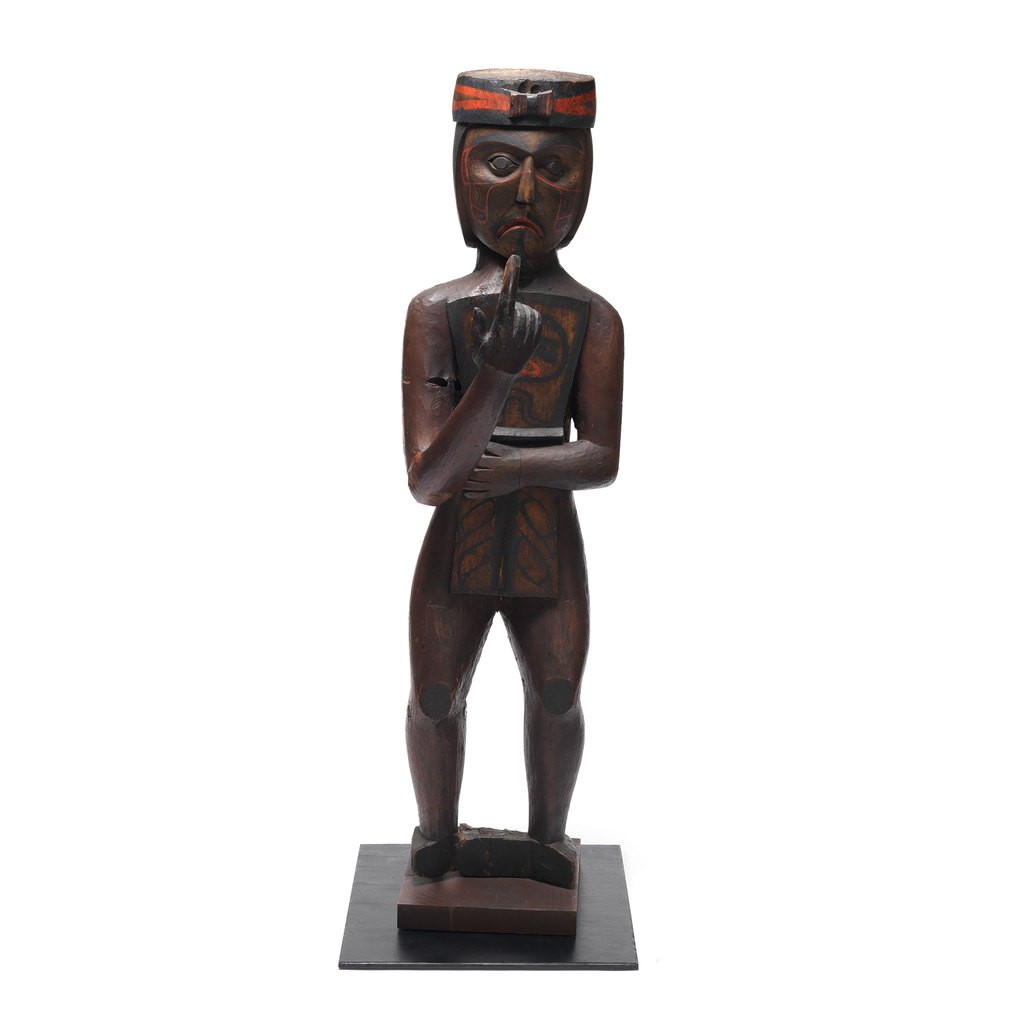 A cedar figure sculpture which is a Kwakwaka'wakw man whose right hand is point to the sky. His left hand is holding a copper.