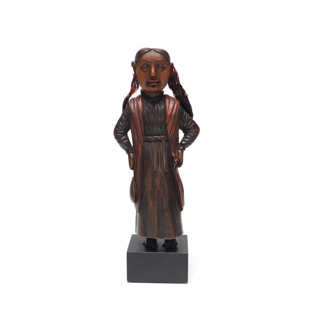 A wooden figure which is a girl with long hair. She wears a dress and puts her hands on her waist.