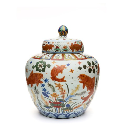 A porcelain jar with fish and water plants patterns on it.