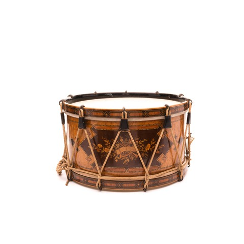 A drum which is made from seven different colours of wood. A floral design is inset on a darker section of wood.