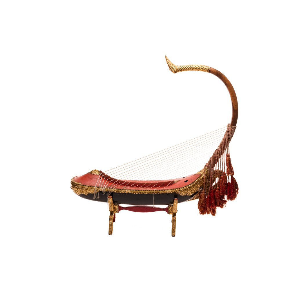 A golden, red and black highly decorative arched harp.