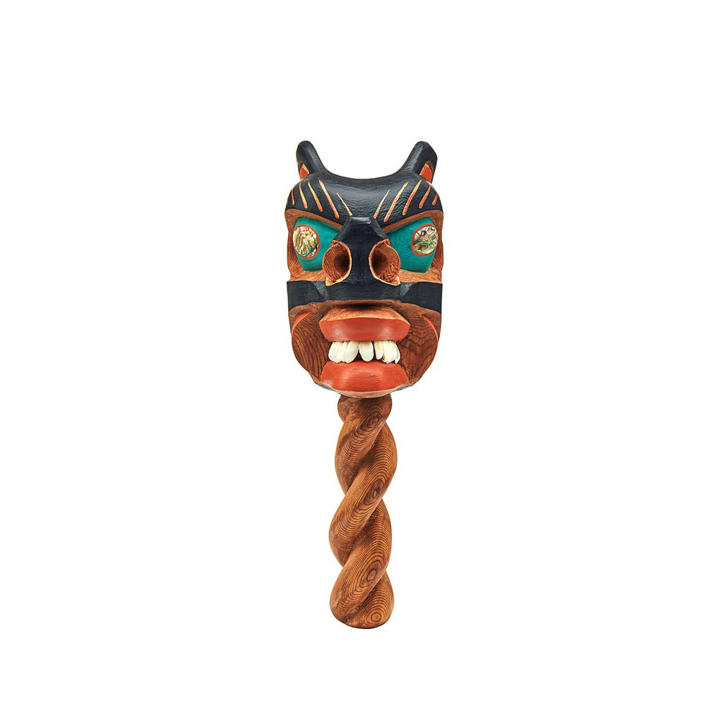 A wooden two-faces rattle. The head presents one wolf face and one human face.