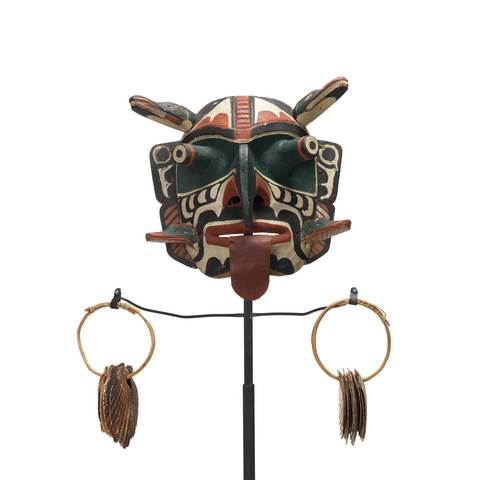 Xwixwi mask representing red snapper or cod, shown with sea shell rattles. Large protruding eyes, drooping tongue, 4 animal figures project from temples and cheeks.