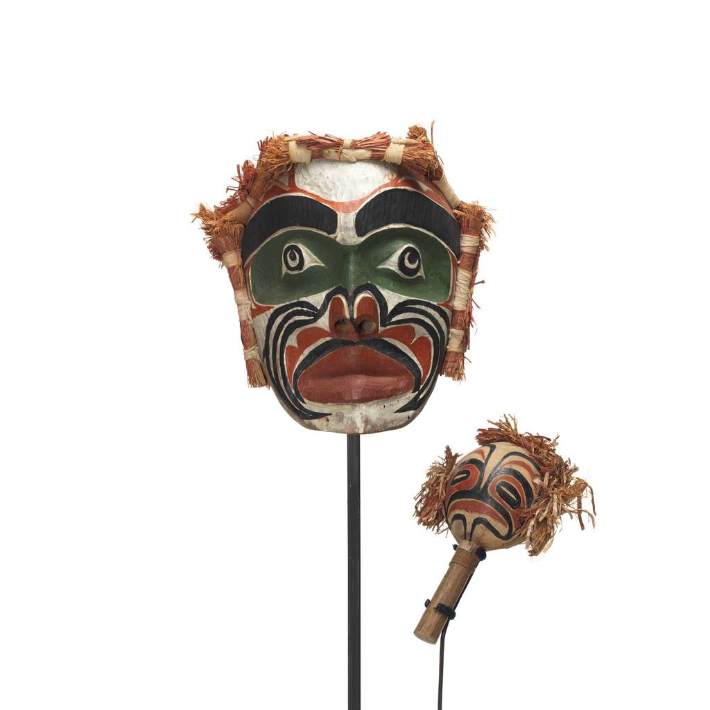 Ancestral spirit mask with rattle, brightly painted in green, white, black and red with cedar bundles top and sides.