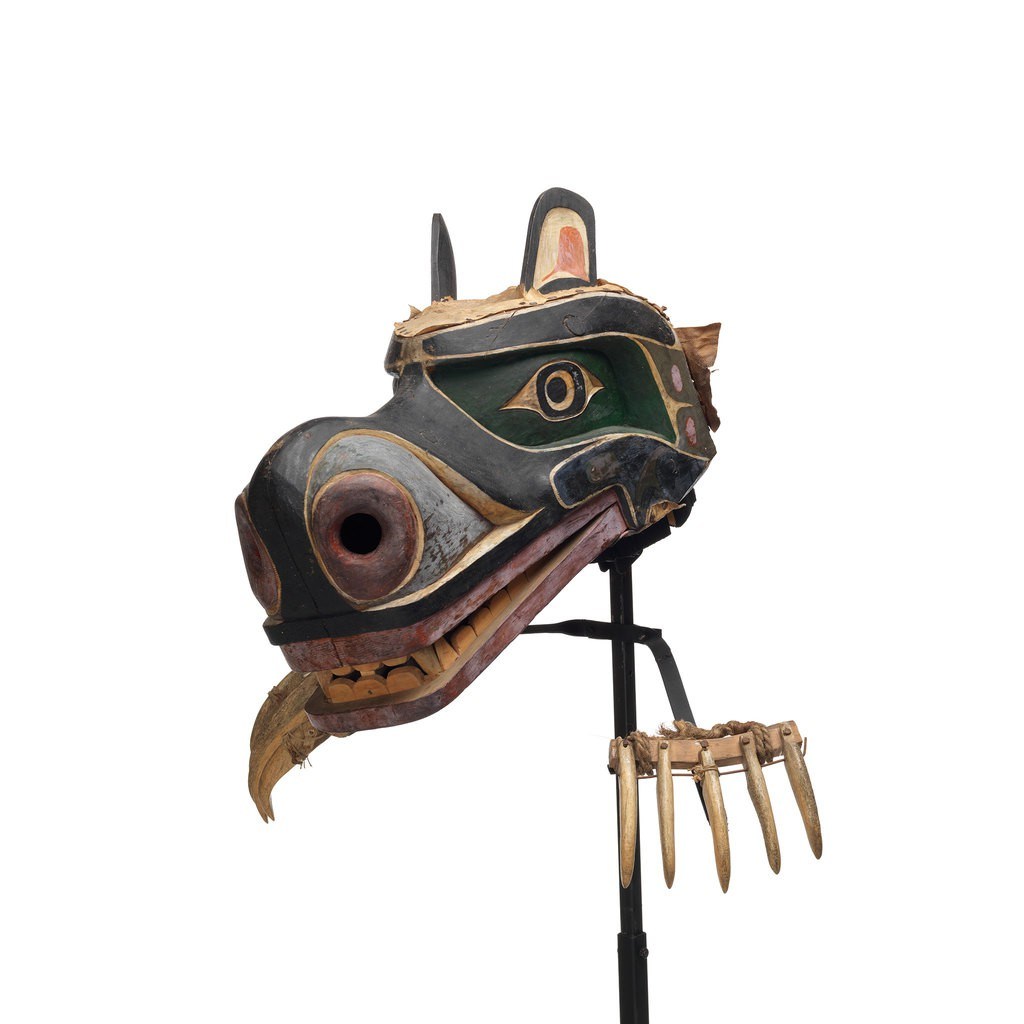Nan or grizzly bear mask with claws made of whale bone, attached to stand by wire supports, mask is painted black and green with red and white detailing.