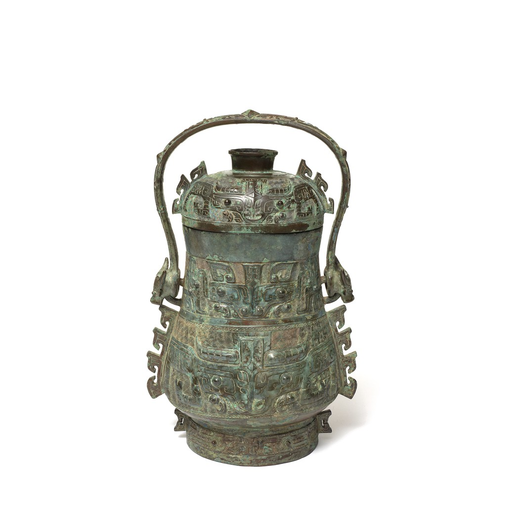 """A bronze wine vessel with six mythical animal """"Taotie""""s' faces on it."""